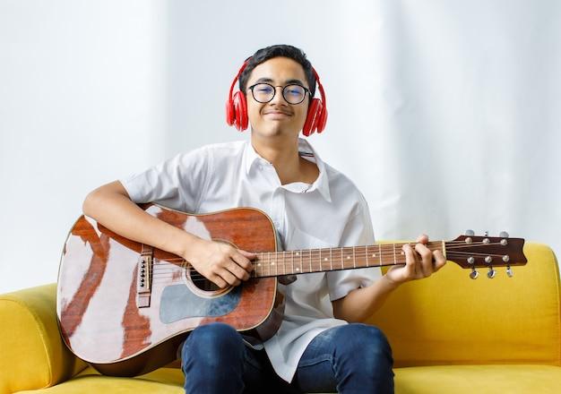 어쿠스틱 기타 연주를 즐기고 빨간 헤드셋을 착용한 잘생긴 젊은 남성 십대의 초상화. 흰색 옷을 입은 주니어 소년 기타리스트는 소파에 앉아서 악기를 들고 있습니다.