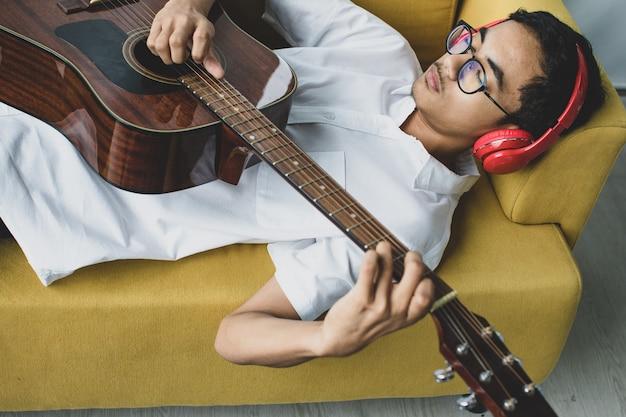 アコースティックギターを弾き、赤いヘッドセットを身に着けているハンサムな若い男性のティーンエイジャーのポートレートショット。ソファに横になって、感情を込めてメロディーを弾きながらリラックスした少年ギタリスト
