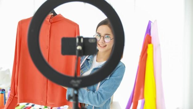 그녀의 새로운 컬렉션을 소비자와 함께 보여주기 위해 젊고 아름다운 아시아 패션 디자이너 화상 통화의 초상화. 그녀는 자신의 컬렉션을 전 세계 사람들에게 판매할 수 있습니다.