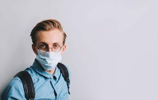 若い男のポートレートショット、バックパックを持つ大学生は透明な眼鏡と医療用使い捨てマスクを着用