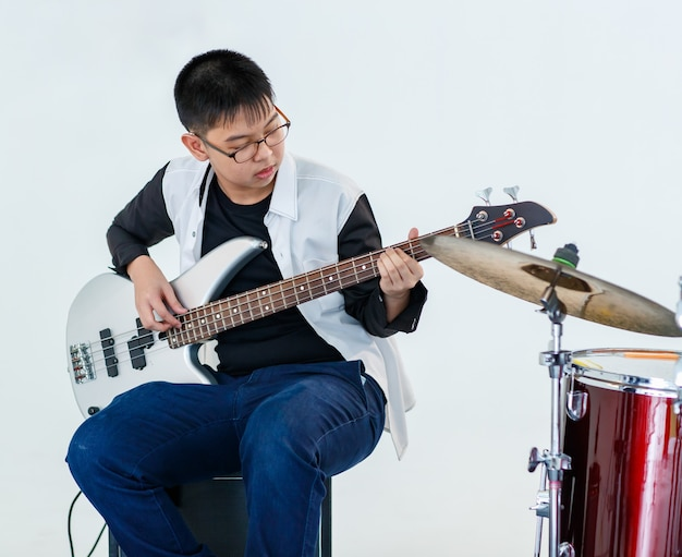 フォアグラウンドでドラムとベースギターを演奏する若い10代のベーシストのポートレートショット。白い背景の楽器を演奏するプロのジュニア男性ミュージシャン。練習の概念