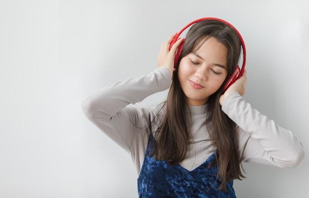 ヘッドセットで音楽を聴いている若いタイ・トルコのティーンエイジャーのポートレートショット。手で音楽を楽しむジュニアガール混血モデルがヘッドホンに触れて目を閉じてジェスチャー。リラックスのコンセプト