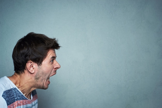 Portrait of shouting man at a gray wall background with copy space. screaming face