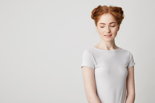 Portrait of shy young pretty redhead girl with buns looking down smiling .