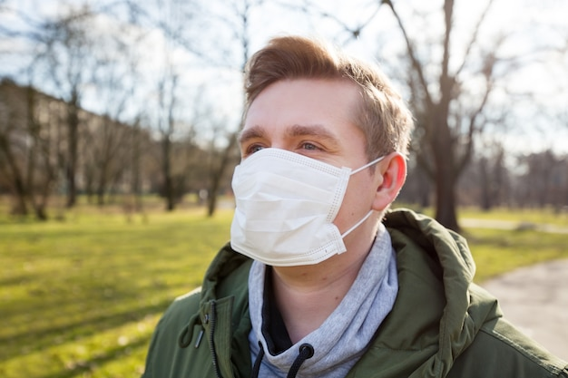Portrait of a sick man wearing medical mask on a city public park bacground. corona virus pandemic. concept of air pollution, pneumonia outbreak, smog or epidemic