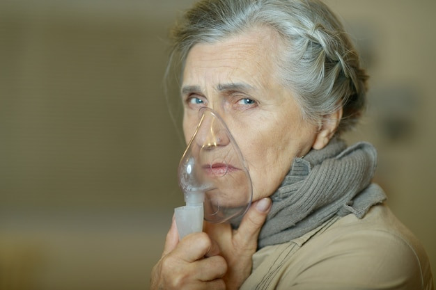 Portrait of a sick old woman making inhalation