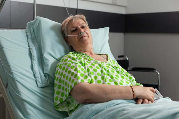 Portrait of sick pensioner woman looking into camera while resting in bed