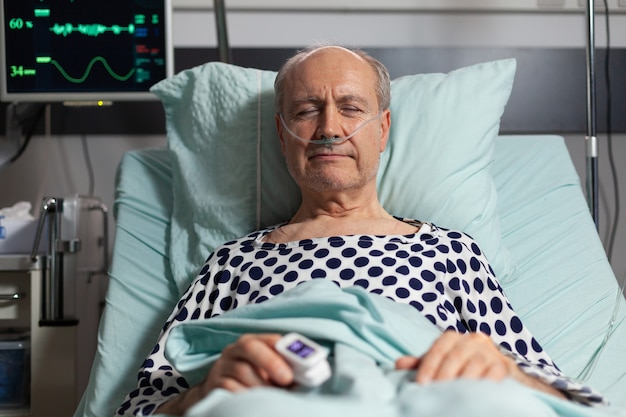 Portrait of sick senior man patient resting in hospital bed, breathing with help from oxygen mask because of lungs infection, having oximeter attached on finger