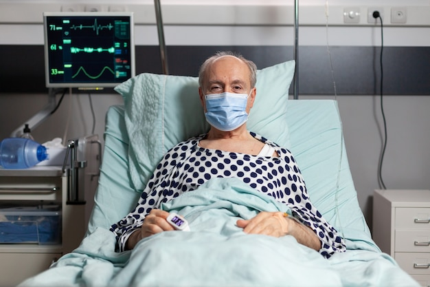 Portrait of sick senior man patient with chirurgical mask resting in hospital bed