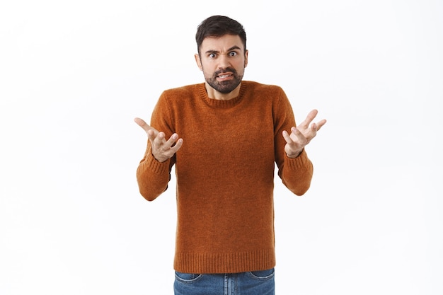 Portrait of sick and tired, frustrated bearded caucasian man arguing, have quarrel, raise hands in dismay, shrugging  confused with annoyed, bothered face, white wall