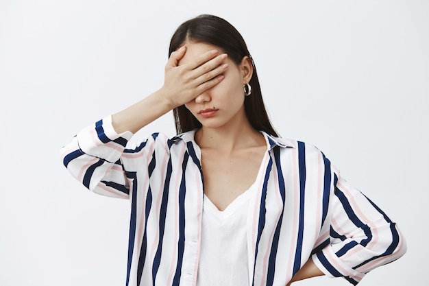 Portrait of sick and tired gloomy woman in striped blouse, holding palm on eyes