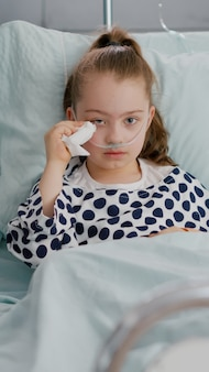 Portrait of sick vulnerable alone little child looking into camera while crying