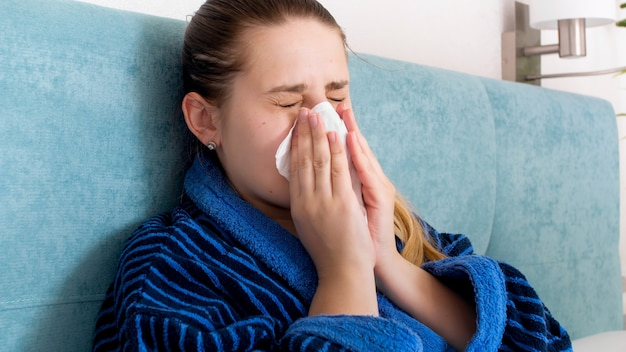 Portrait of sick woman with cold blowing runny nose in paper tissue.
