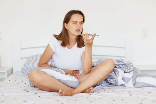 Portrait of sick woman with dark hair wearing white casual t shirt sitting on bed, holding mobile phone, recording voice message to her doctor, suffering from stomachache.