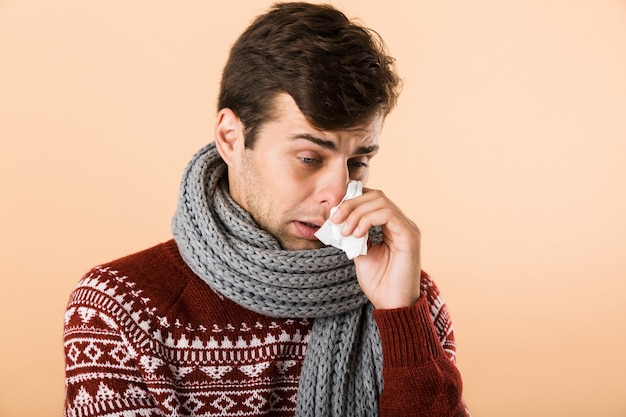 Portrait of a sick young man dressed in sweater and scarf