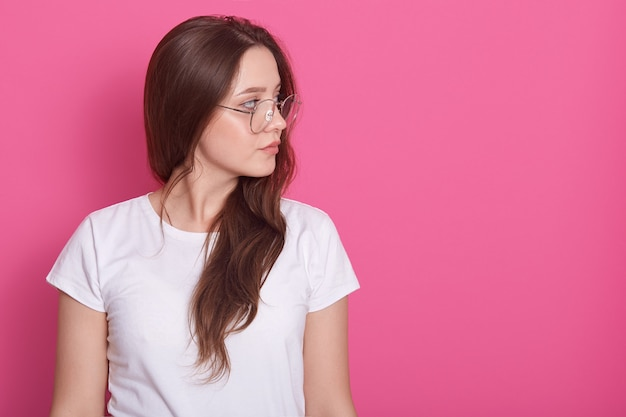 Portrait side profile of beautiful woman with long hair, dressed whitr casual t shirt and glasses, looking aside