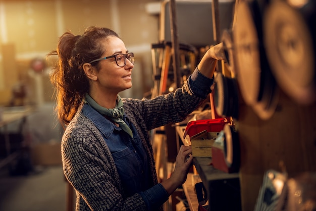 Portrait side view of happy attractive hardworking middle aged professional female carpenter worker choosing tools in the workshop or garage.