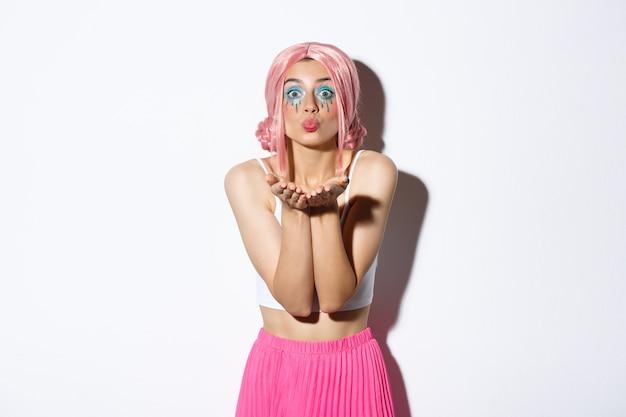Ritratto di sciocca bella ragazza caucasica con trucco luminoso, vestita per la festa in parrucca rosa glam, che soffia bacio d'aria alla macchina fotografica, in piedi.