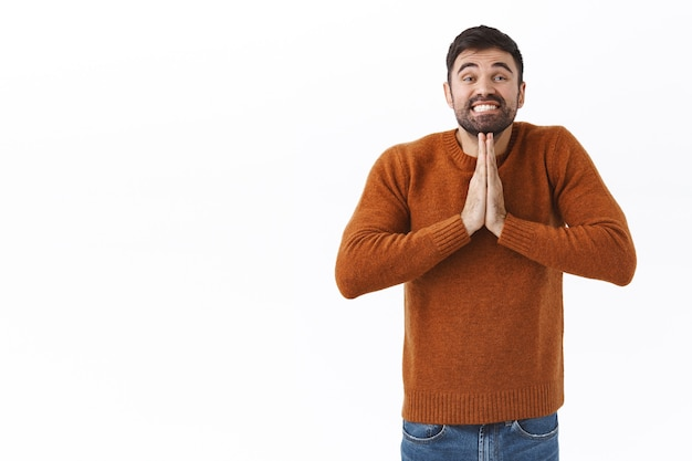 Portrait of silly and cute smiling handsome man, begging for help, need advice, asking for offer, holding hands in pray and smiling, want and say please, standing white wall hopeful