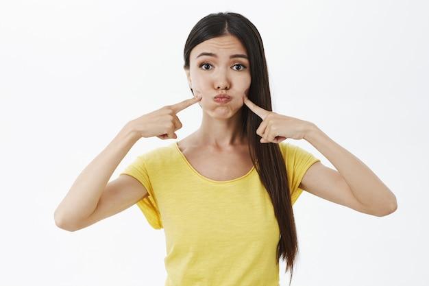 Ritratto di sciocco modello femminile e carino femminile in maglietta gialla che fa il broncio trattenendo il respiro e colpendo le guance con le dita indice