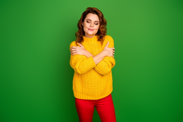 Portrait of sincere calm charming woman hug herself enjoy bright winter fall sweater wear style stylish trendy pants isolated over shine color wall