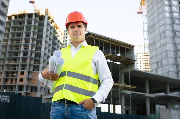 Portrait of site manager posing with blueprints against unfinished building