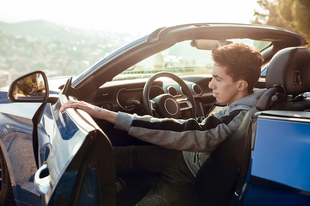 Portrait of sitting boy in luxury sports car opening door at sunrise