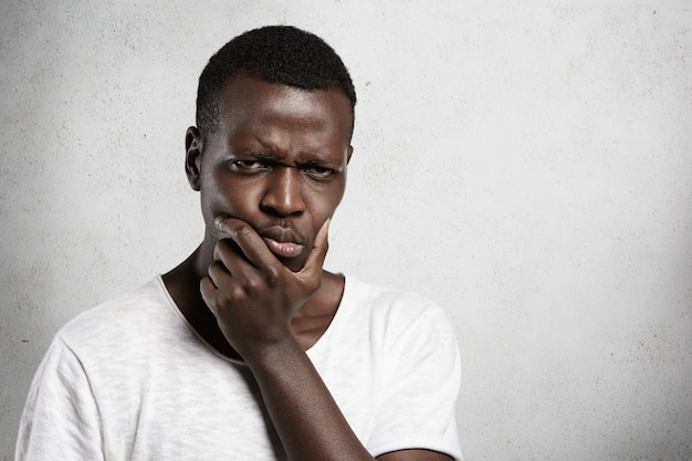 Portrait of skeptical african young man looking with suspicious or annoyed expression, holding hand on chin, doubting, thinking over something.