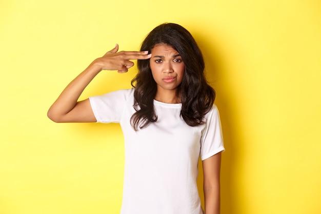 Ritratto di donna afroamericana scettica e infastidita che fa segno con la pistola a dito sopra la testa