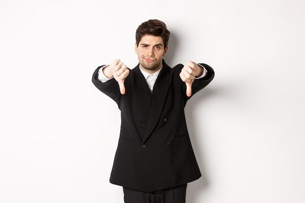 Ritratto di uomo scettico e deluso in abito nero, accigliato sconvolto, mostrando pollice verso, antipatia per qualcosa di brutto, in piedi su sfondo bianco.