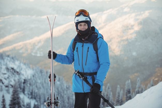 Portrait of skier standing with ski
