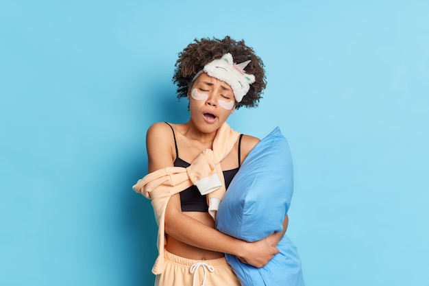 Portrait of sleepy curly haired afro american woman yawns after early awakening holds pillow dressed in pajama and sleepmask tilts head applies collagen pads under eyes isolated over blue wall