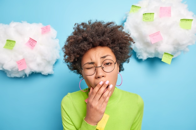 Portrait of sleepy curly woman yawns and covers mouth has exhausted face expression wears big round spectacles worked late hours poses against white clouds with reminding sticky notes