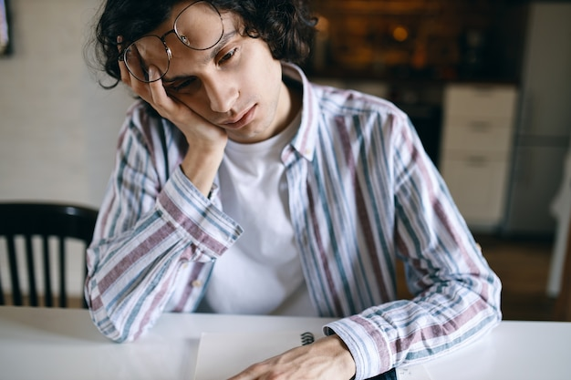 Portrait of sleepy male student in casual clothing sitting at white desk holding hand on his face, having bored look, being tired of doing homework, needs some sleep.