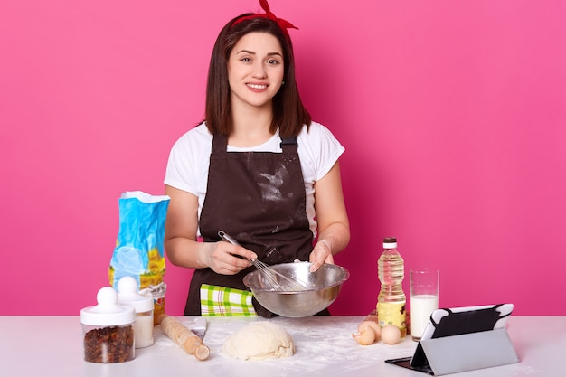 Portrait of slender skillful attractive cook standing at kitchen, mixing ingredients with whisk, looking directly at camera, looks cheerful. magnetic cute woman follows tv show on her tablet.