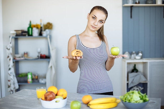 Portrait of a slim attractive woman making a choice between an apple and a sweet bun