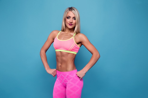 Portrait of slim sporty blonde bodybuilder. very hot woman stand