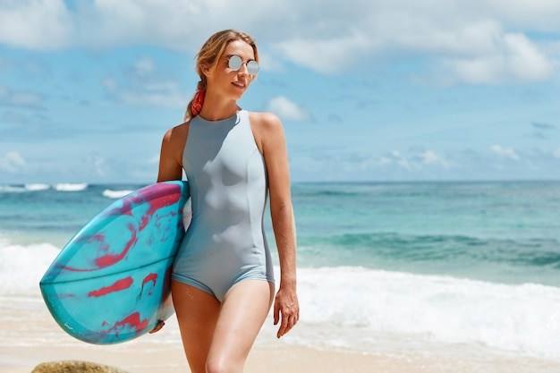 Portrait of slim woman in blue bathing suit and trendy sunglasses enjoys sunny day on ocean beach, likes surfing, carries surf board, waits for windy weather conditions to go in for sport on waves