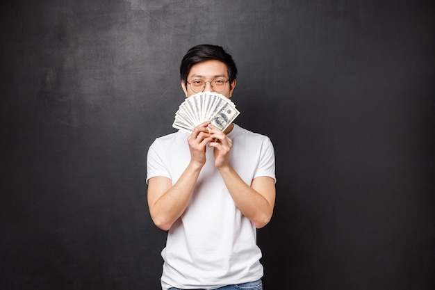 Portrait of sly happy and pleased asian young man winning big cash prize money, hiding face behind fan of dollars smiling with eyes, decide what to buy on it, standing
