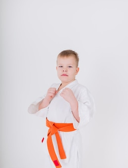 Portrait of a small boy in a white kimono with an orange belt standing in a pose on a white wall