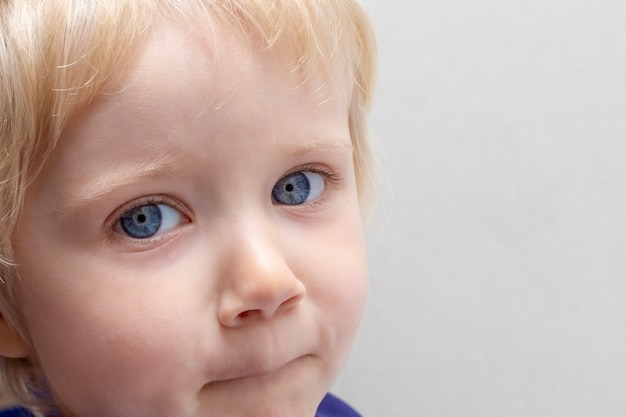 Portrait of a small child with blond hair, blue eyes, light skin on a gray background. copy space to the right.