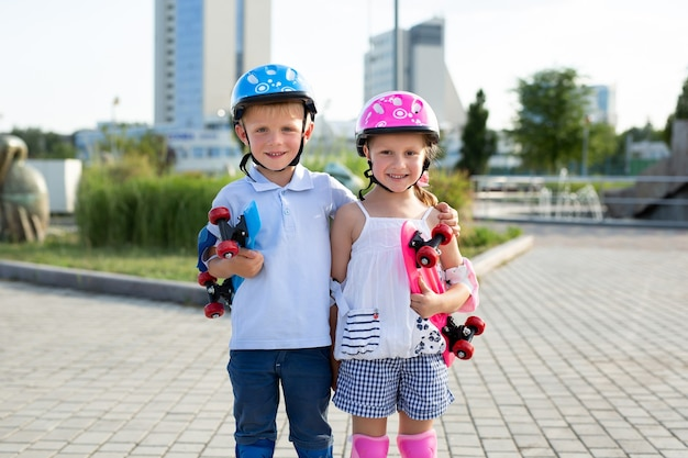 Portrait of small children of a boy and a girl in a park with skates