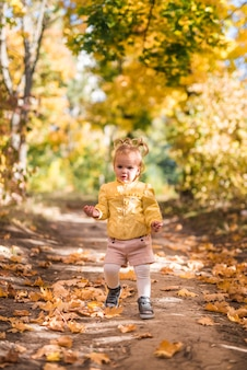 Portrait of a small girl standing in forest trail during autumn