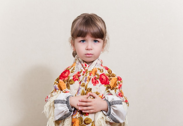 Portrait of small pretty girl in traditional ukrainian costumes on white background