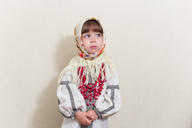 Portrait of small pretty girl in traditional ukrainian style.young beautiful girl in a  long white national shirt and traditional scarf. ukrainian culture, ethno style