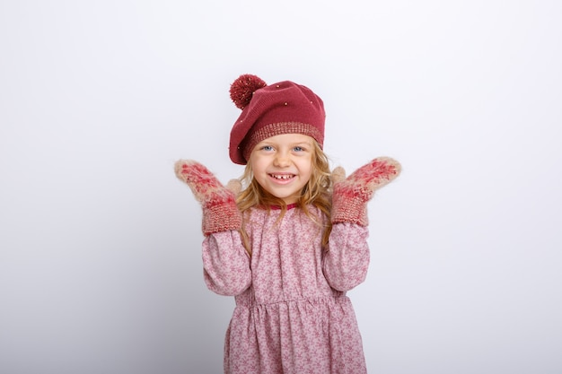 Portrait of a small smiling girl on a gray background