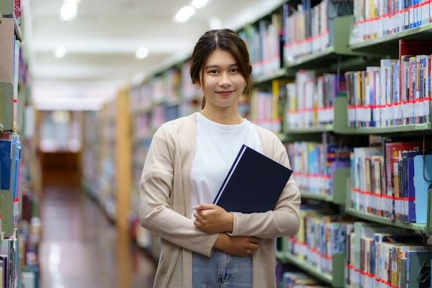 Portrait of smart asian woman university student reading book and looking at camera between bookshelves in campus library with copyspace.