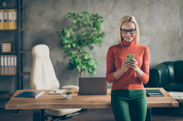 Portrait of smart company owner woman use smartphone chatting with employees colleagues stand near wooden table in office loft wear red turtlneck
