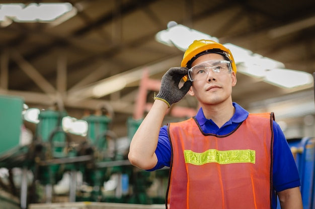 Portrait of smart engineer asian chinese happy labor worker handsome model in heavy industry