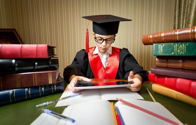 Portrait of smart girl in graduation cap playing on digital tablet